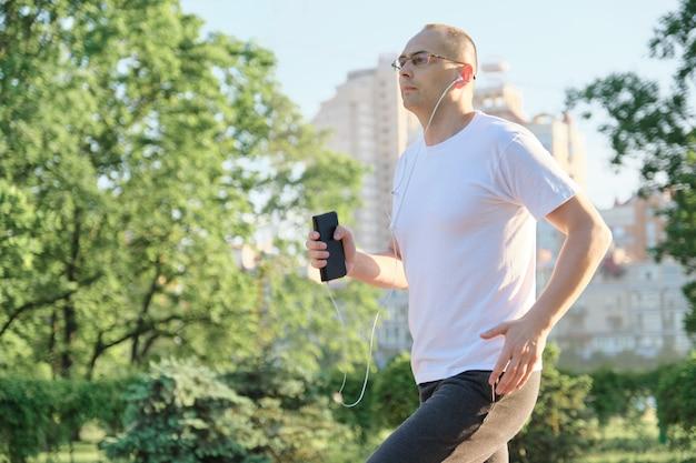 Man van middelbare leeftijd met een bril loopt door stadspark met koptelefoon