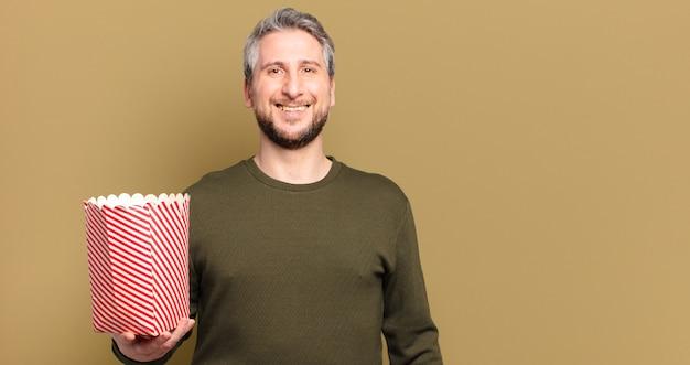 Man van middelbare leeftijd met een emmer popcorn