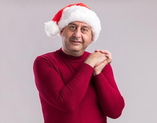 Man van middelbare leeftijd met een kerstmuts die elkaars hand vasthoudt met een glimlach op het gezicht over een witte muur