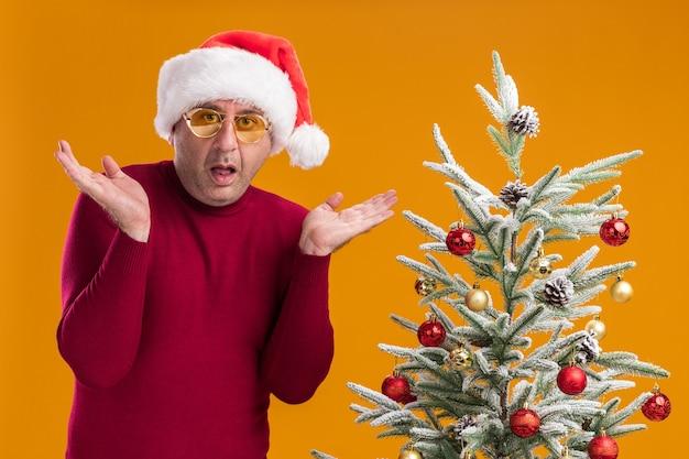 Man van middelbare leeftijd met een kerstmuts in een donkerrode coltrui en een gele bril die verward zijn armen naar de zijkanten spreidt die naast een kerstboom over een oranje muur staat