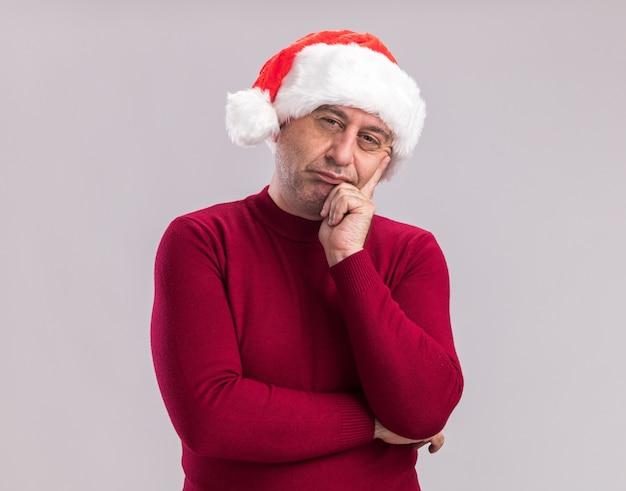 Man van middelbare leeftijd met een kerstmuts met een sceptische uitdrukking over een witte muur
