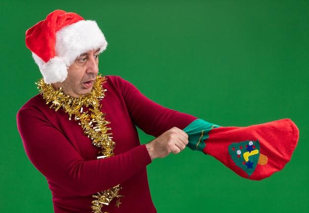 Man van middelbare leeftijd met een kerstmuts met klatergoud om de nek die een kerstsok vasthoudt en er verward naar kijkt terwijl hij over de groene muur staat