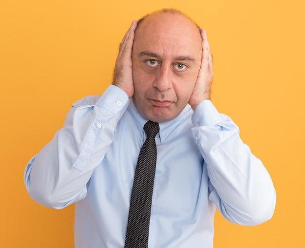 Man van middelbare leeftijd met een wit t-shirt met stropdas bedekt oren geïsoleerd op een oranje muur