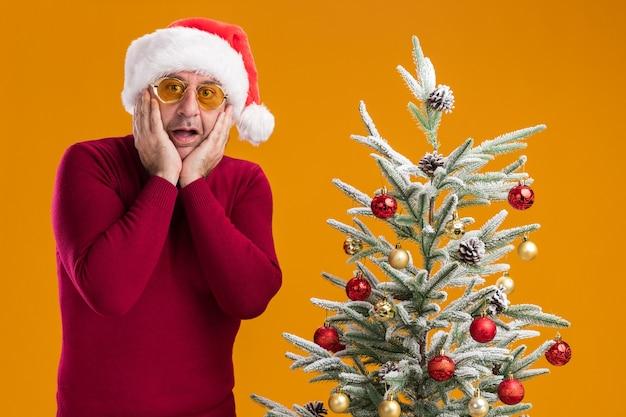 Man van middelbare leeftijd met kerst-kerstmuts in donkerrode coltrui en gele bril camera kijken verbaasd en verbaasd naast een kerstboom staan op oranje achtergrond