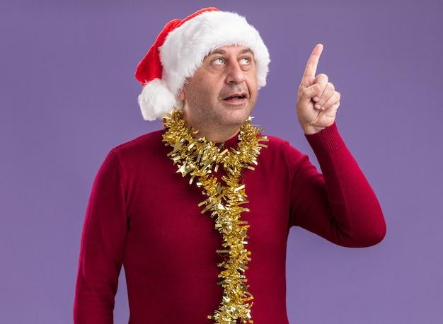Man van middelbare leeftijd met kerst kerstmuts met klatergoud om nek opzoeken met glimlach op slim gezicht wijsvinger met nieuw idee staande over paarse achtergrond tonen