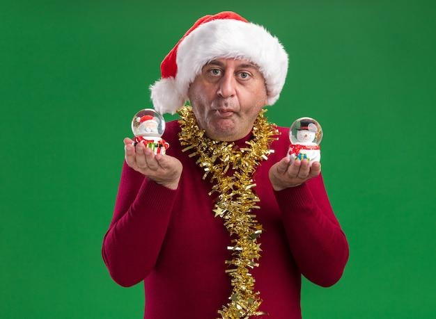 Man van middelbare leeftijd met kerst kerstmuts met klatergoud rond de nek houden kerst sneeuwbollen kijken camera verward staande over groene achtergrond
