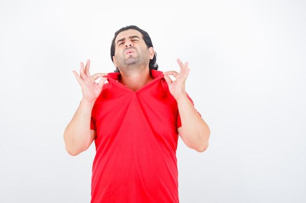 Man van middelbare leeftijd met kraag terwijl hij zich warm voelt in een rood t-shirt en verveeld kijkt, vooraanzicht.