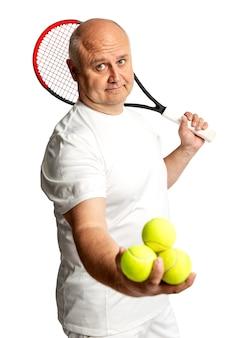 Man van middelbare leeftijd met racket en tennisballen. geã¯soleerd op een witte achtergrond. verticaal