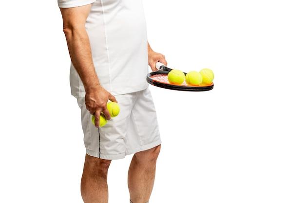 Man van middelbare leeftijd met racket en tennisballen. geã¯soleerd op een witte achtergrond.