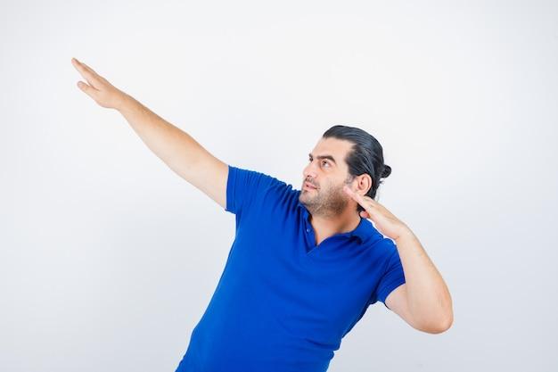 Man van middelbare leeftijd mikken met het strekken handen in blauw t-shirt en op zoek gericht. vooraanzicht.