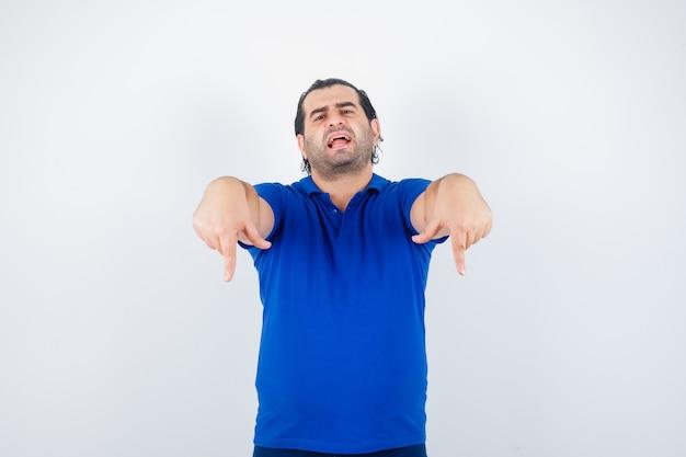 Man van middelbare leeftijd naar beneden wijzend in blauw t-shirt en op zoek naar vertrouwen. vooraanzicht.
