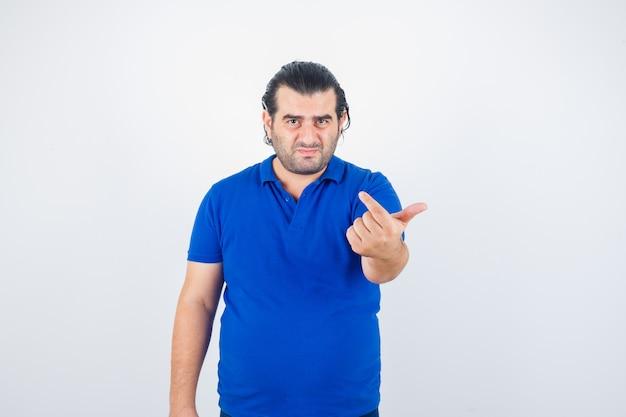 Man van middelbare leeftijd nodigt uit om in polot-shirt te komen en kijkt verontrust, vooraanzicht.