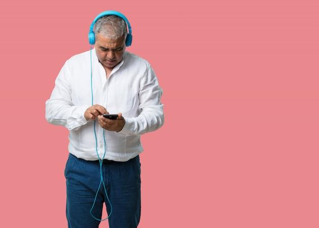 Man van middelbare leeftijd ontspannen en geconcentreerd, luisterend naar muziek met zijn mobiele telefoon, voel het ritme en ontdek nieuwe artiesten, ogen dicht