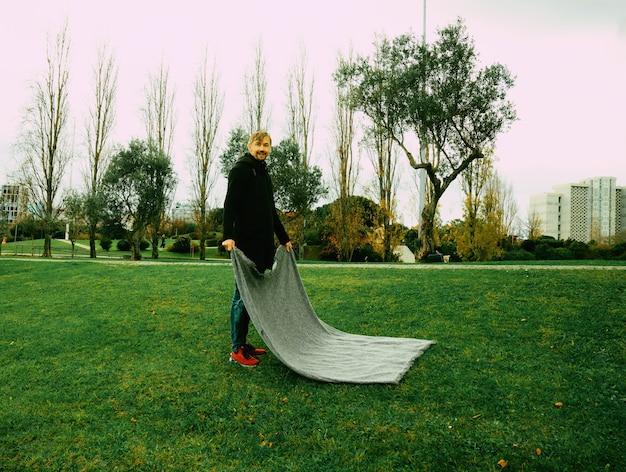 Man van middelbare leeftijd ontvouwen deken in het park. geestelijk gezondheidsconcept. isolatie, eenzaamheid, tijd alleen, rituelen en social distancing concept