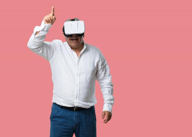Man van middelbare leeftijd opgewonden en bezig, spelen met virtual reality-bril, een fantasiewereld verkennen, iets proberen aan te raken