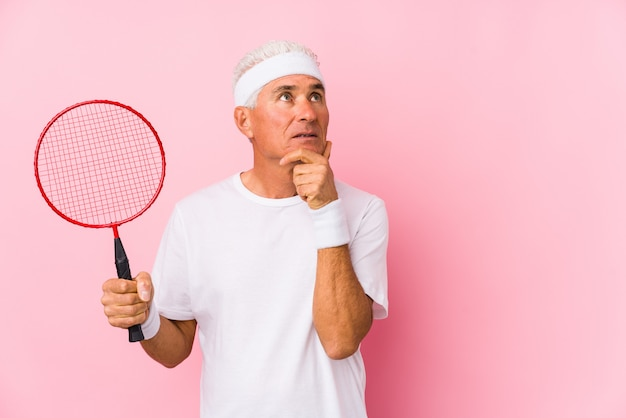Man van middelbare leeftijd spelen badminton geïsoleerd opzij kijken met twijfelachtige en sceptische uitdrukking.