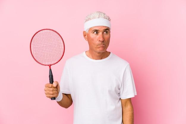 Man van middelbare leeftijd spelen badminton geïsoleerd verward, twijfelachtig en onzeker.