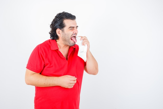 Man van middelbare leeftijd tong afvegen met servet in rood t-shirt en walgen, vooraanzicht op zoek.