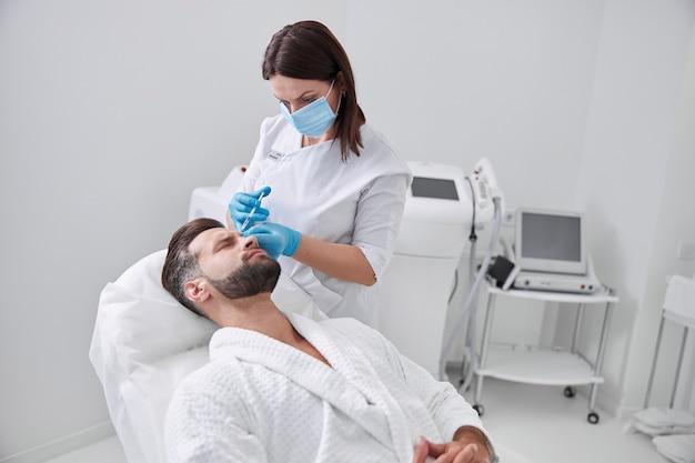 Man van middelbare leeftijd trekt een grimas van pijn terwijl schoonheidsspecialiste in de kliniek een injectie met opheffende vuller doet