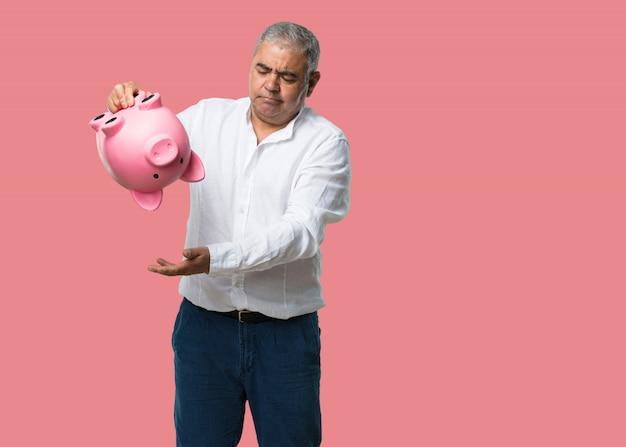 Man van middelbare leeftijd, verdrietig en teleurgesteld, met een biggenbank, geen geld over, probeert iets uit te halen, gezicht van woede en angst, concept van armoede