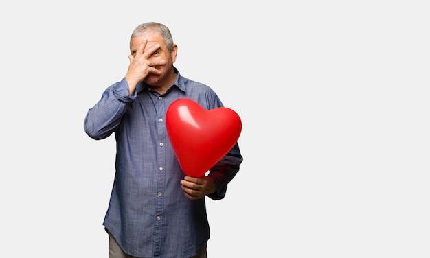 Man van middelbare leeftijd vieren valentijnsdag pijnlijk en lachen op hetzelfde moment
