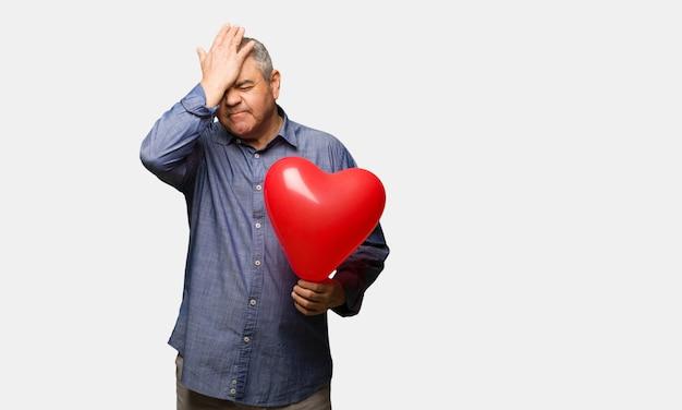 Man van middelbare leeftijd vieren valentijnsdag vergeetachtig, realiseren iets