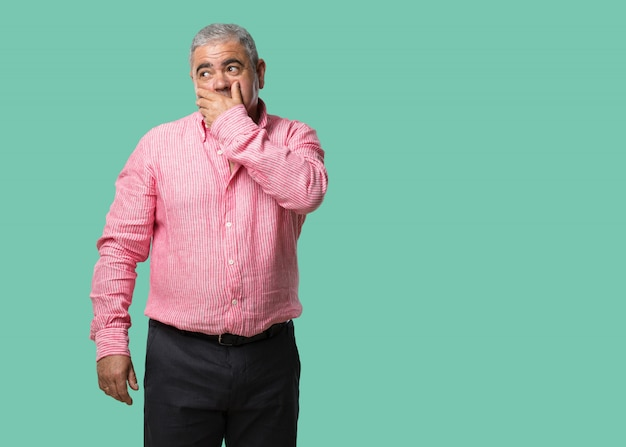 Man van middelbare leeftijd voor mond, symbool van stilte en repressie, proberend niets te zeggen