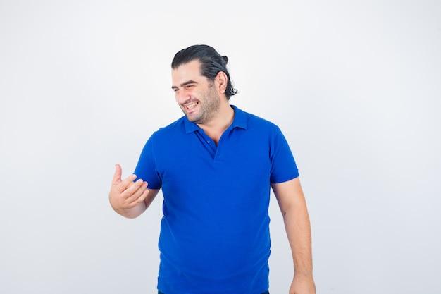 Man van middelbare leeftijd wegkijken in blauw t-shirt en op zoek vrolijk, vooraanzicht.