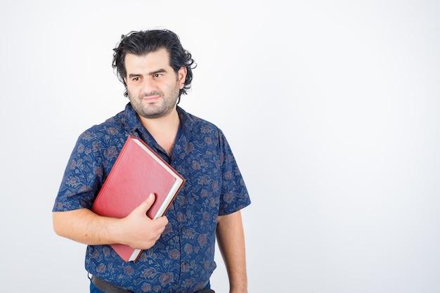 Man van middelbare leeftijd wegkijken terwijl hij boek in shirt vasthoudt en zelfverzekerd kijkt, vooraanzicht.