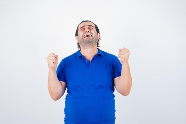 Man van middelbare leeftijd winnaar gebaar in blauw t-shirt tonen en op zoek gelukkig. vooraanzicht.