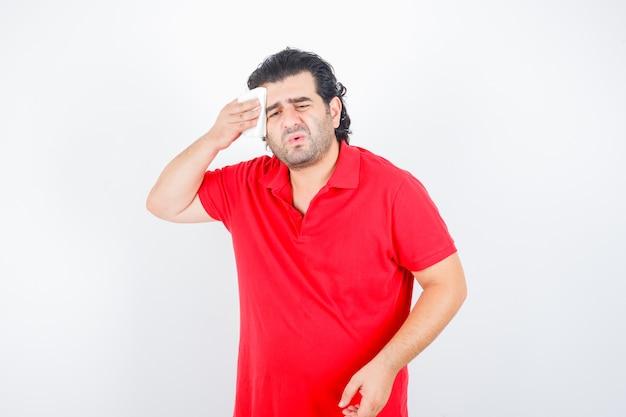 Man van middelbare leeftijd zweet in rood t-shirt afvegen en ziek, vooraanzicht kijken.