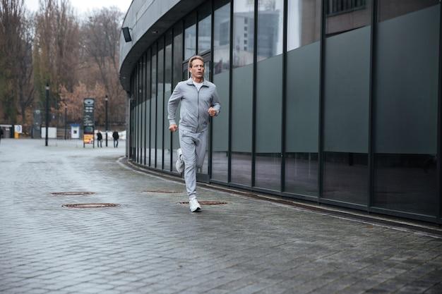 Man van volledige lengte in grijze sportkleding die op straat loopt