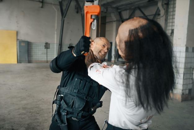 Man vecht met wrede zombie in verlaten fabriek. horror in de stad, griezelige beestjes, doomsday apocalyps, bloody evil monster