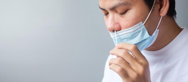 Man veegt covid-19-test af met rapid antigen test-kit. coronavirus zelf-nasale of thuistest, lockdown en home isolation-concept