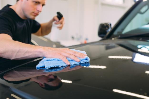 Man veegt met een stoffen lijf van een schitterende auto.
