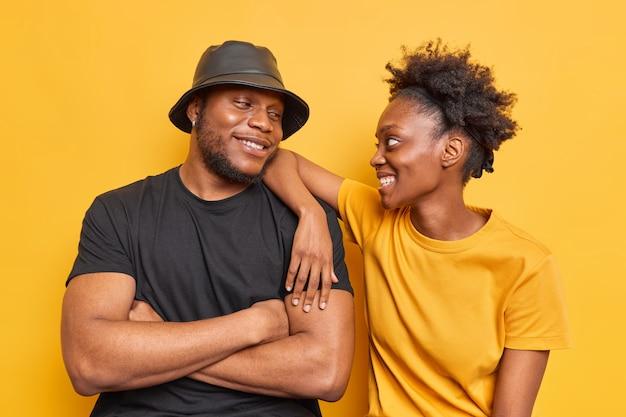 Man veel plezier kijken graag naar elkaar dragen casual gele en zwarte t-shirt pose binnen. gelukkig tienermeisje met krullend haar leunt op de schouder van de beste vriend