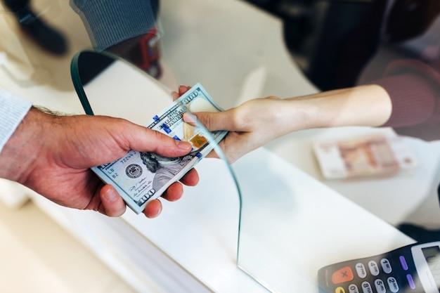 Man verandert geld in een wisselkantoor, een groot bedrag aan dollars, een stijging van de wisselkoers, close-up een geldwisselende handen van mensen