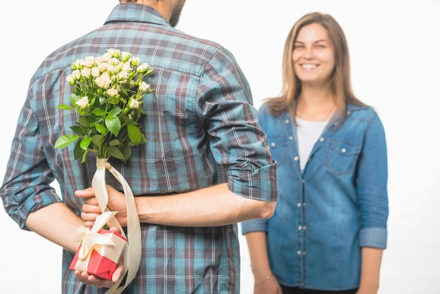 Man verbergt een geschenkdoos en bloeit achter zijn rug en geeft verrassing aan zijn vriendin Gratis Foto
