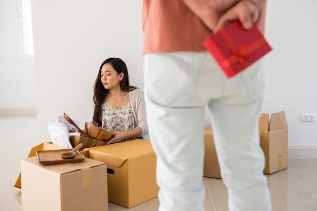 Man verbergt verrassingsgeschenk om aan aziatische vrouw te geven tijdens onverpakte spullen op kartonnen dozen. verrast cadeau voor vrouw van de eerste dag die naar een nieuw huis verhuist. start een nieuw paarleven. gelukkig man en vrouw.