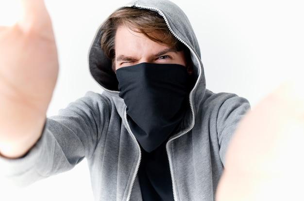 Man verbergt zijn gezicht onder een masker met een kap anonimiteit misdaad diefstal close-up