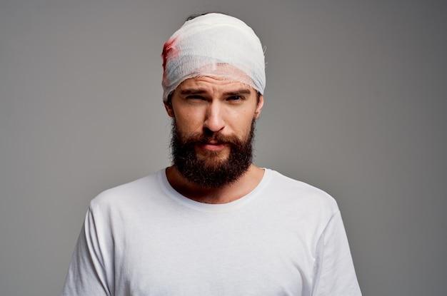 Man verbonden hoofd en hand bloed lichte achtergrond. hoge kwaliteit foto