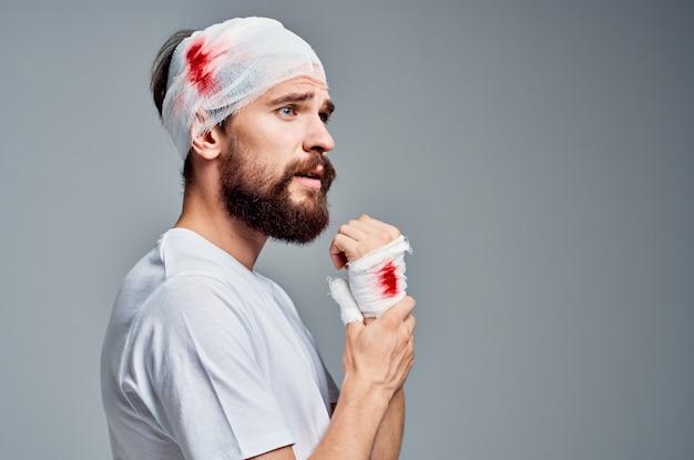 Man verbonden hoofd en hand bloed lichte achtergrond