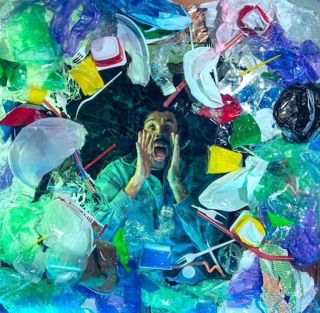 Man verdrinkt in water onder stapel van plastic recipiënten, afval. gebruikte flessen en pakken die de oceaan vullen en mensen doden.