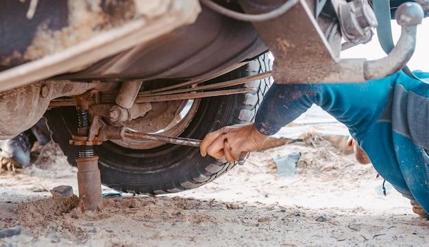 Man verhoogt op een jack 4x4 off-road truck