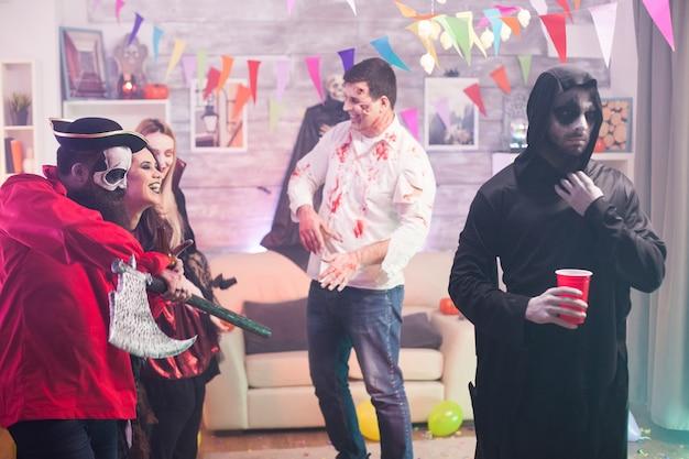 Man verkleed als een boze magere hein op halloween-feest.