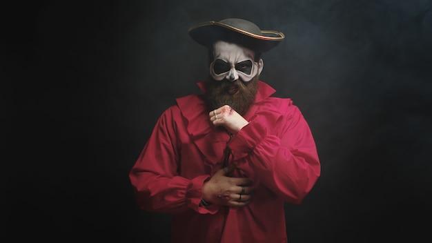 Man verkleed als een enge piraat in rood shirt en met een hoed voor halloween op zwarte achtergrond.