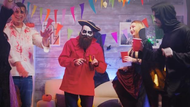 Man verkleed als een piraat die danst met mensen verkleed als verschillende monsters op halloween-feest.