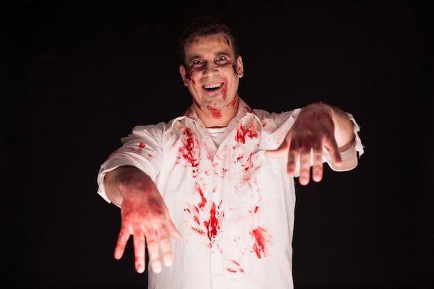 Man verkleed als een zombie bedekt met bloed op zwarte achtergrond.