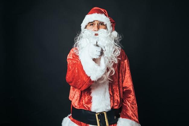 Man verkleed als kerstman met vinger wijzend op camera, op zwarte achtergrond. kerstconcept, kerstman, geschenken, feest.