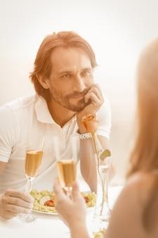 Man verliefd kijkt gelukkig naar zijn vrouw. gelukkige volwassen paar vieren evenement of datum in café aan de zeekust buitenshuis.